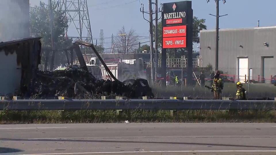 Des pompiers arrosent des carcasses de véhicules.