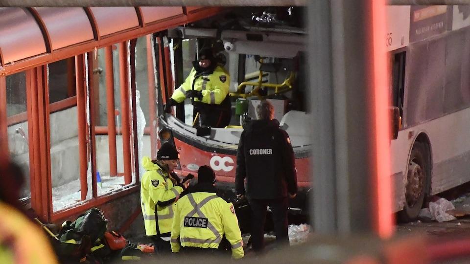 Des policiers en uniforme d'hiver devant un autobus accidenté