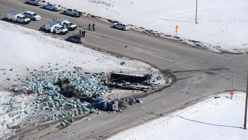 Un camion renversé et les restes d'un autocar à une intersection où sont assemblés plusieurs véhicules d'urgence.