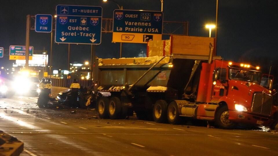 Un véhicule accidenté derrière un camion.