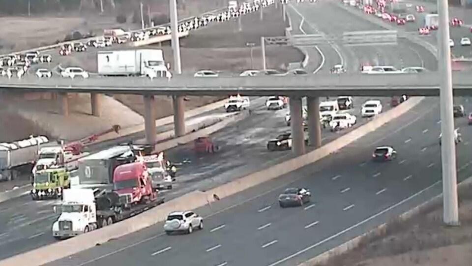 Photo de camions sur l'autoroute fermée, des files de voitures dans d'autres voies.