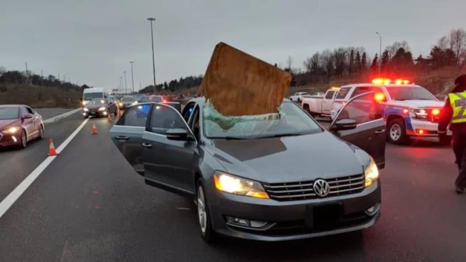 Un gros morceau de contreplaqué écrasé à travers le pare-brise d'un véhicule
