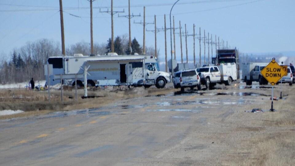 De nombreux véhicules, des camions et des voitures, sont stationnés sur la route et sur le bord de la route. En avant-plan une affiche qui incite à ralentir.