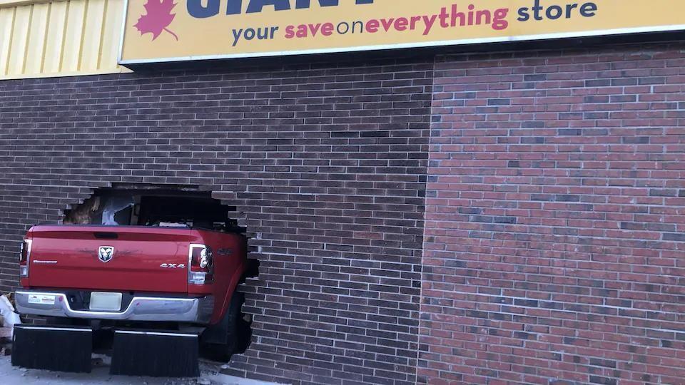 Un camion dans un mur de brique.