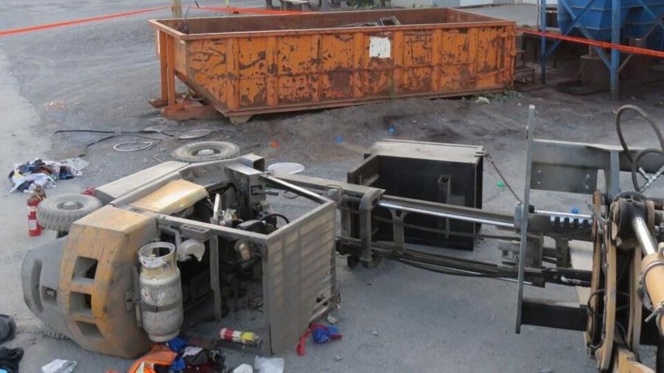Scène de l'accident, un chariot élévateur est renversé près d'un conteneur.