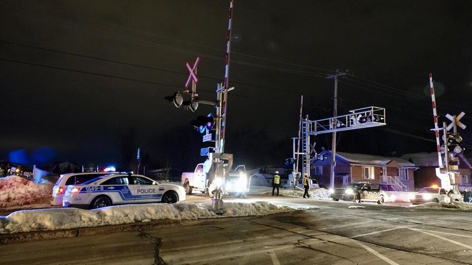 Des voitures de police au passage à niveaux.
