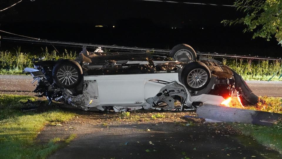 La voiture est renversée sur le toit.