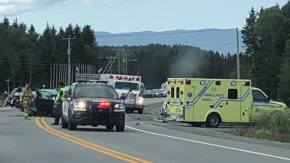 Une voiture de police et une ambulance sont immobilisés sur la route près d'une scène d'accident.