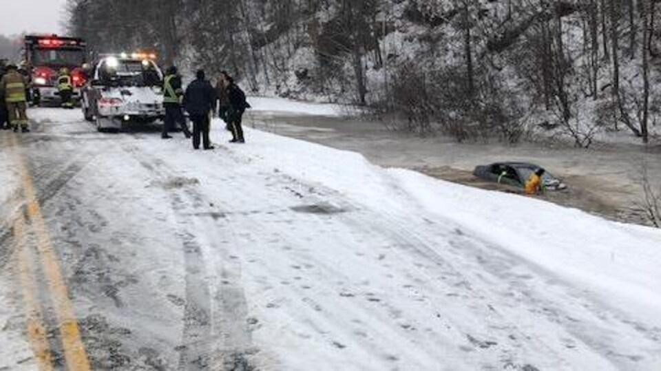 Des pompiers et une équipe de remorquage discutent sur la route près de la voiture immergée dans l'étang en bas du talus.