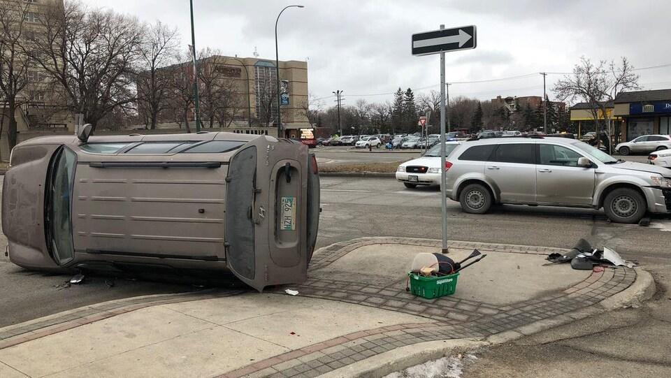 Un véhicule renversé sur le côté au coin d'une rue, devant la voiture qui l'a emboutie et une autopatrouille.