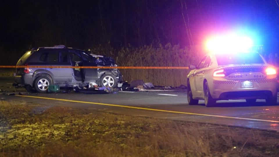 La voiture accidentée derrière un ruban de sécurité.