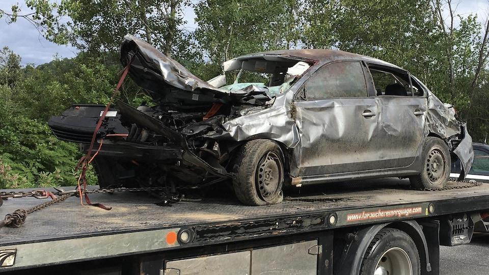 Une voiture endommagée à la suite d'un accident, installée sur une remorque.