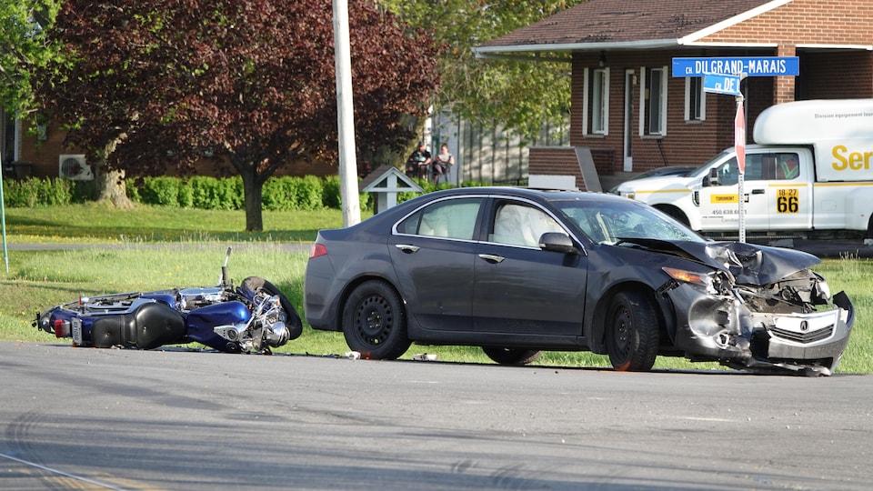 Une auto fracassée et la moto de la victime.