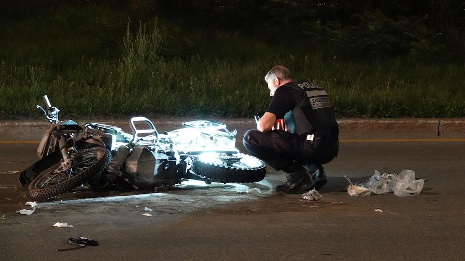 Un policier à côté d'une moto accidentée.