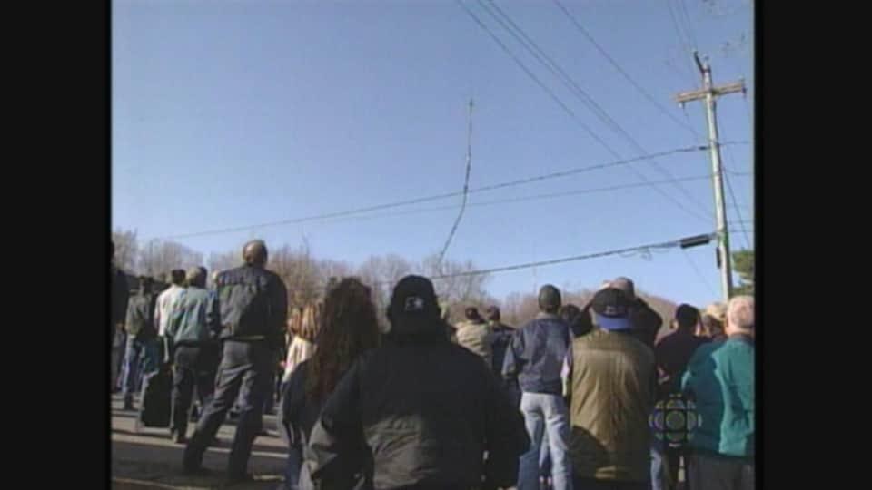 Plusieurs personnes observent une tour s'effondrer.