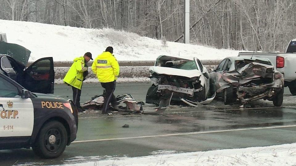 Des inspecteurs de la Police provinciale de l'Ontario inspectent les débris laissés par la collision.