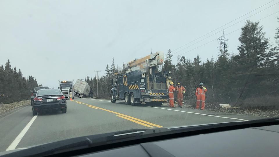 Une remorqueuse tente de sortir un poids lourd d'une fâcheuse position sur la route 138. Il y a aussi un camion d'Hydro-Québec sur place.