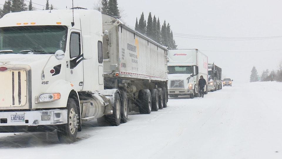 Des camions lourds sont immobilisés sur une route, à la queue leu leu.
