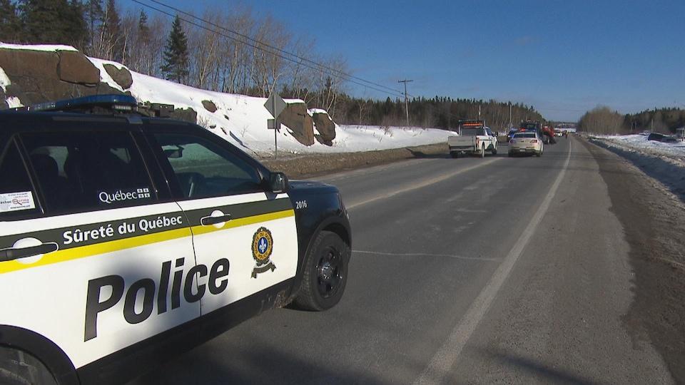 Une voiture de police bloque la route.
