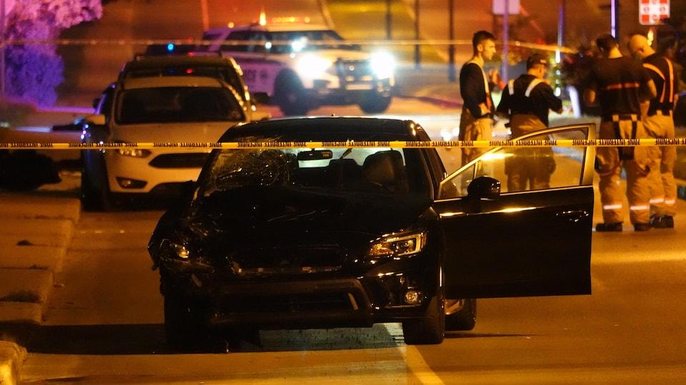 Une voiture accidentée, du ruban jaune et des premiers répondants.