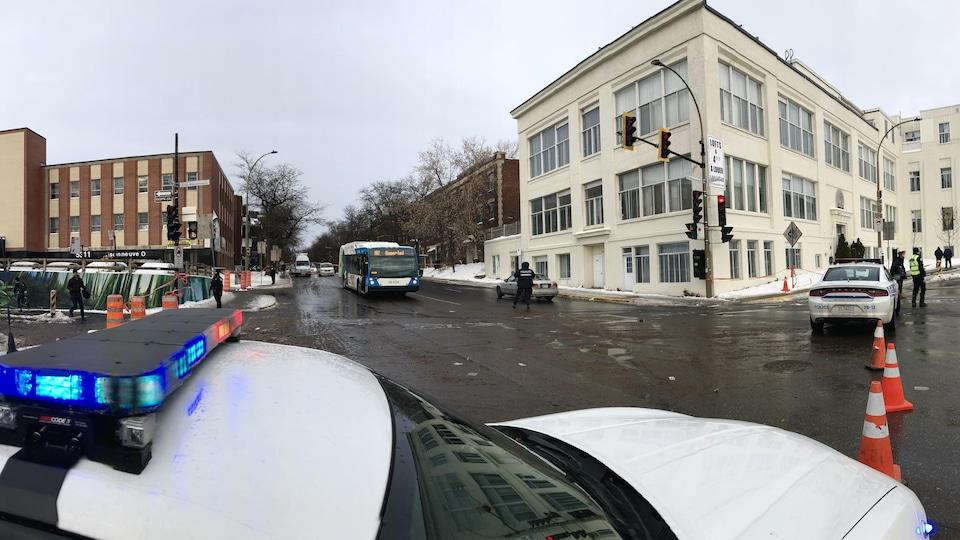 Deux voitures de police bloquent une intersection à Montréal.