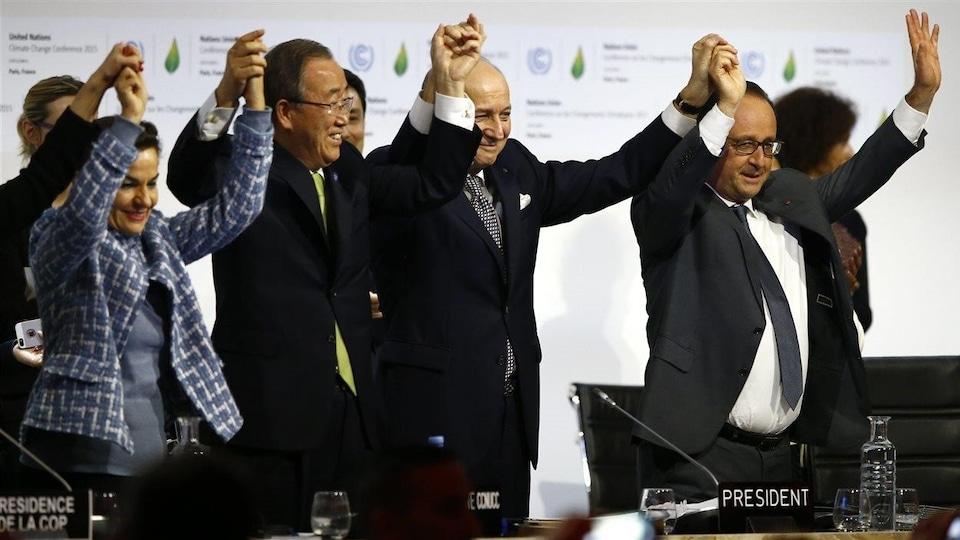 Christiana Figueres, secrétaire exécutive de la Convention-cadre des Nations unies sur les changements climatiques, Ban Ki-moon, secrétaire général des Nations unies, Laurent Fabius, président de la conférence de Paris, et François Hollande, président de la République française, lèvent leurs bars dans les airs en se tenant par les mains.