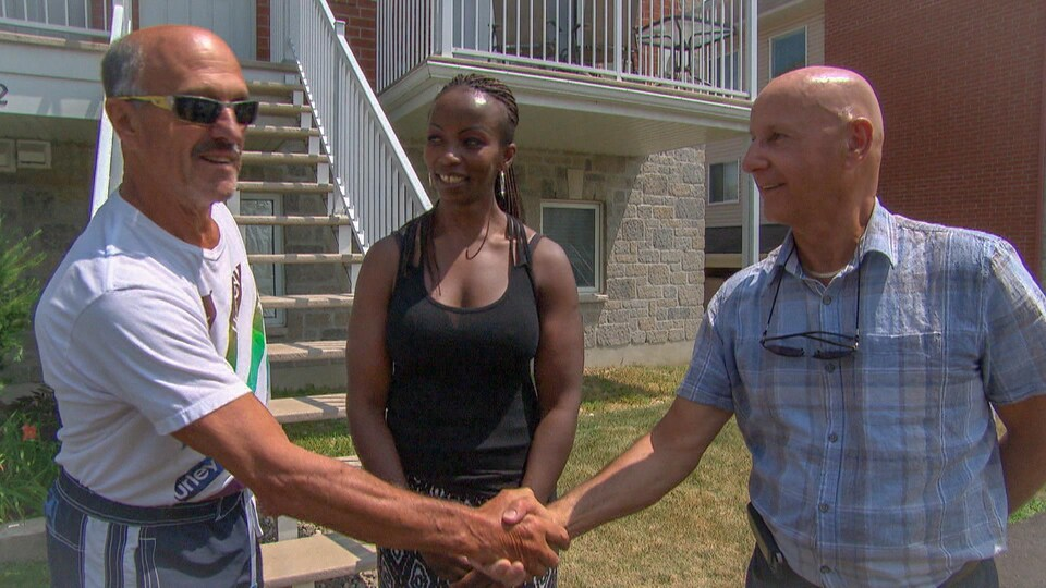 Deux hommes se serrent la main et une femme les regarde.
