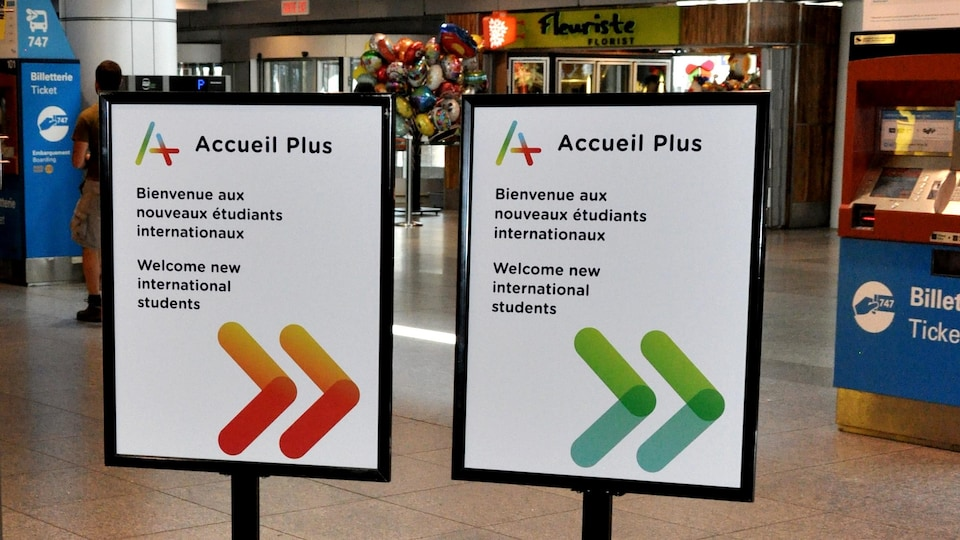 """Deux affiches à l'aéroport Pierre-Elliott-Trudeau de Montréal indiquent avec des flèches pointant à droite: """"Accueil Plus, Bienvenue aux nouveaux étudiants internationaux"""" et ce, en français et en anglais."""