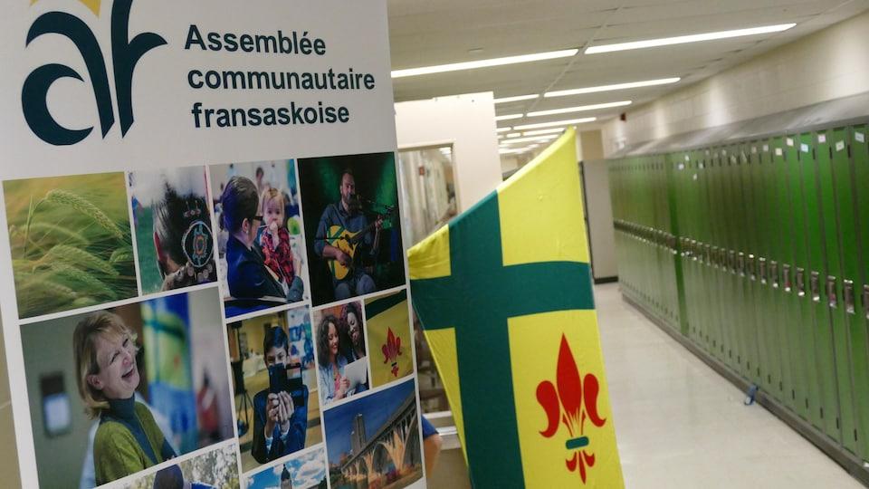 Dans un couloir d'école avec une rangée de casiers, une bannière promotionnelle de l'ACF avec un collage de photos de personnes souriantes, et un drapeau de la Saskatchewan.