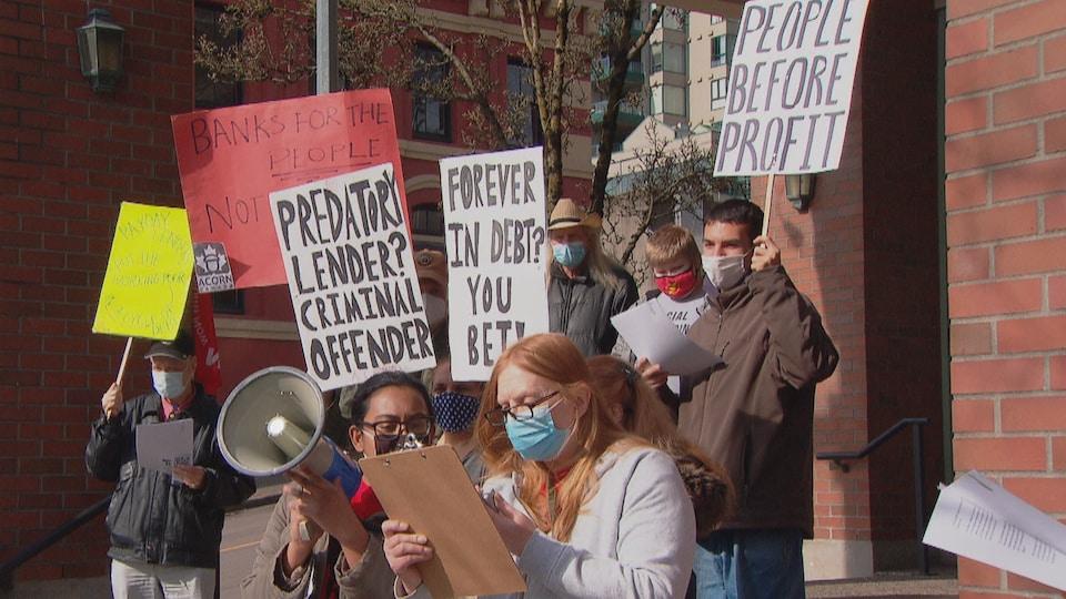 Une dizaine de personnes sont postées au coin d'une rue et montrent leurs pancartes avec des slogans en anglais.