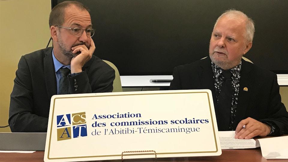 Deux hommes parlent lors d'une conférence de presse derrière une affiche de l'Association des commissions scolaires de l'Abitibi-Témiscamingue.