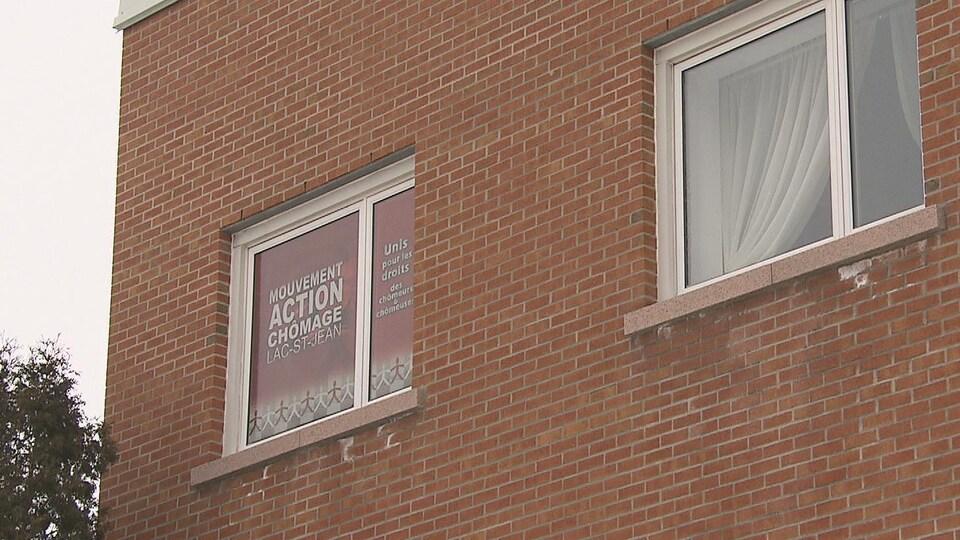 Affiche du mouvement Action Chômage Lac-Saint-Jean dans la fenêtre des locaux.