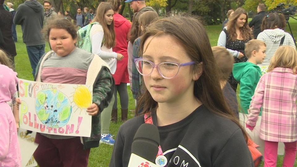 Ada Dechene donne une entrevue. Elle se tient debout près des autres manifestants.