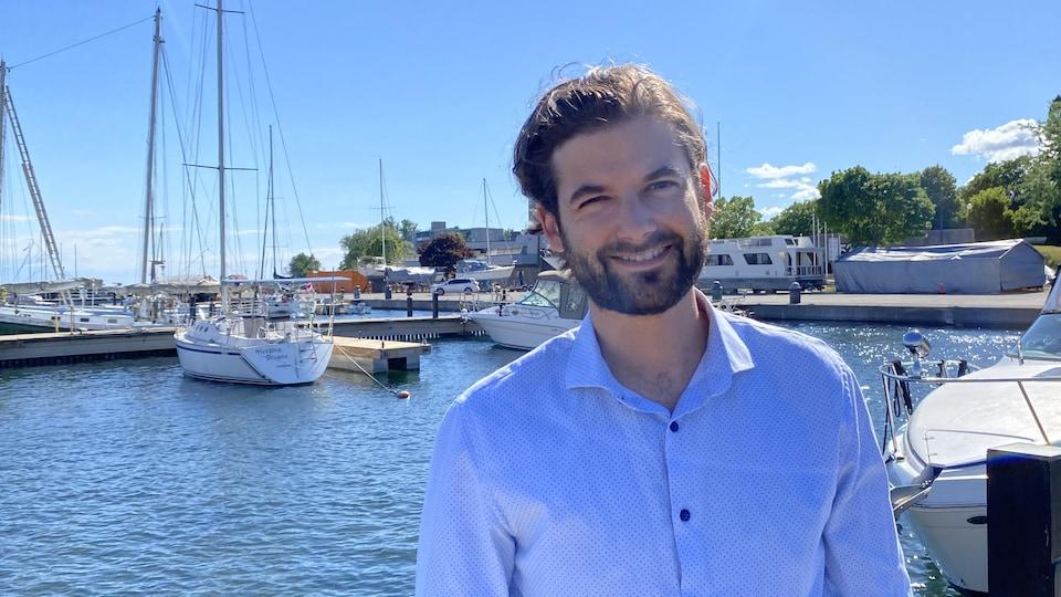 Adam Allore devant des bateaux de plaisance ancrés au quai.