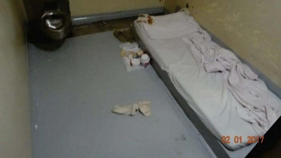 Un lit par terre et une toilette dans une cellule de prison.