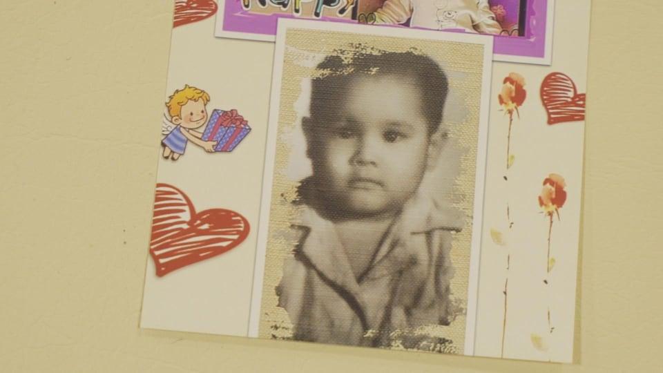 Une photo d'enfant épinglée à un mur.