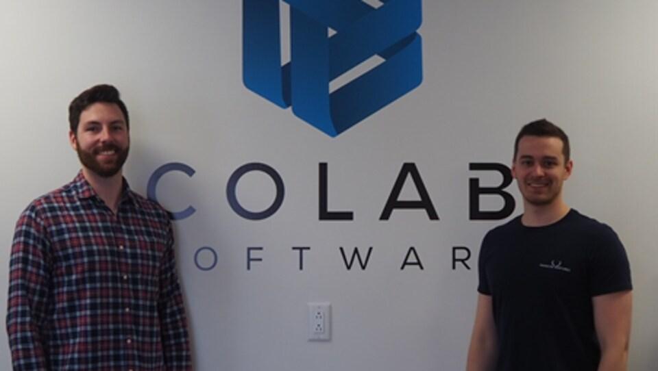 Les deux hommes devant le logo de leur entreprise