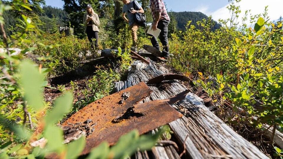 Un groupe marche sur les vestiges d'une cabane en rodins abandonnée.
