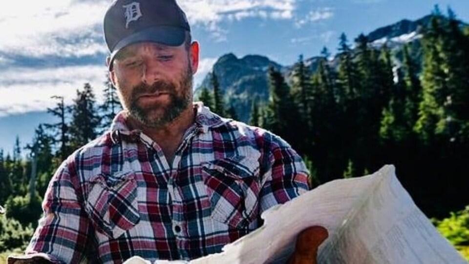 Un homme regarde une carte dans les montagnes de la Colombie-Britannique.