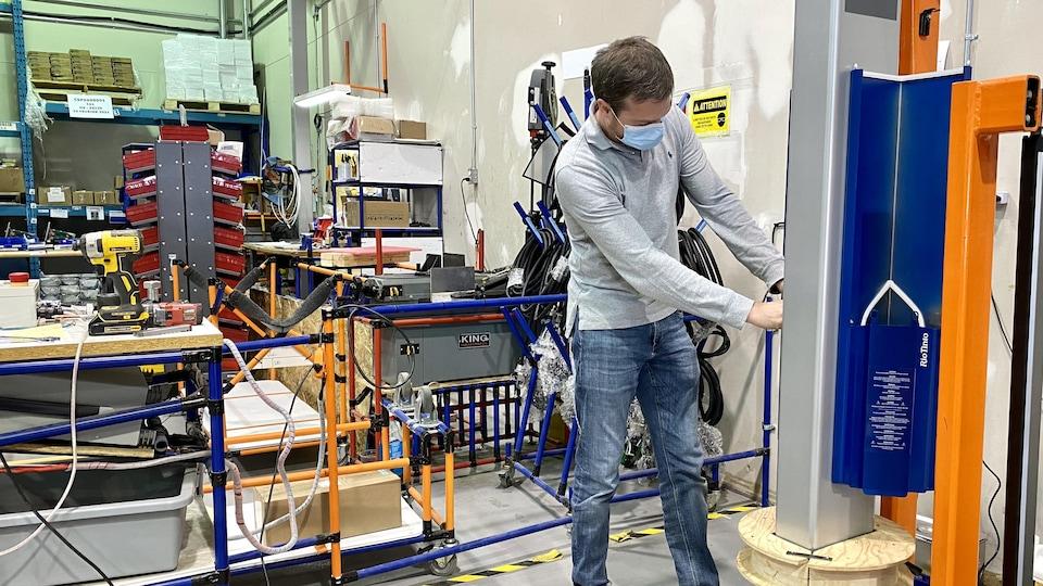 Un homme travaille sur une borne de recharge électrique dans une usine.