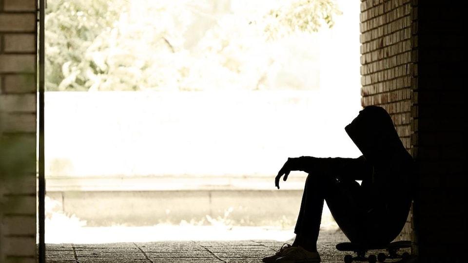 Silhouette d'un jeune assis sur une planche à roulettes.