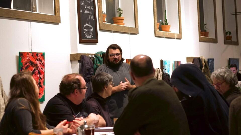 L'écrivain discute dans un café devant quelques personnes.