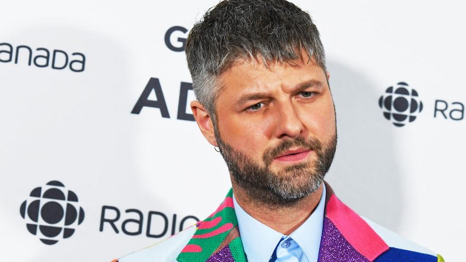 Un homme avec un regard sérieux est vêtu d'un veston avec plusieurs textures, plusieurs formes géométriques et plusieurs couleurs vives.