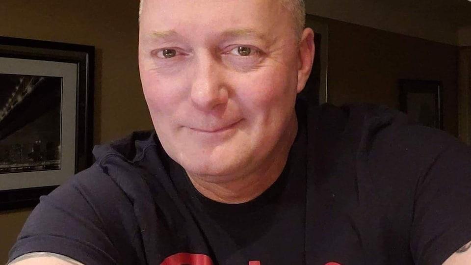Un homme sourit à la caméra en prenant un égo-portrait.