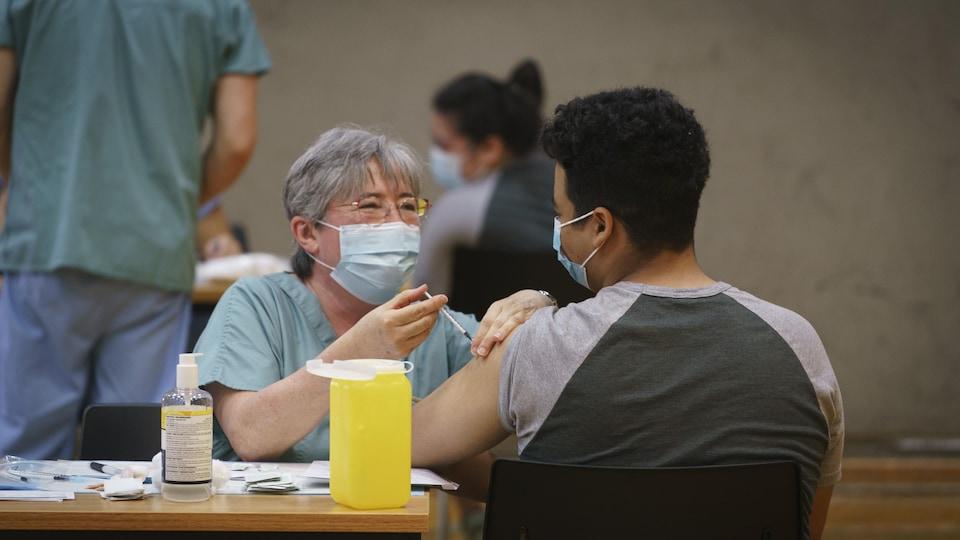 Un adolescent se fait vacciner.