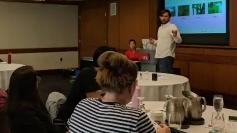 Adolfo Gonzalez debout parle aux participants devant un écran lors de l'atelier sur le cannabis à Vancouver