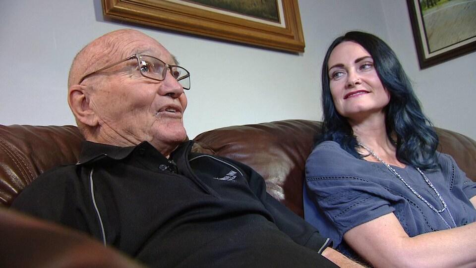 Bob Roger et Adriana Brown assis dans un canapé en cuir. Adriana regarde son père en souriant.
