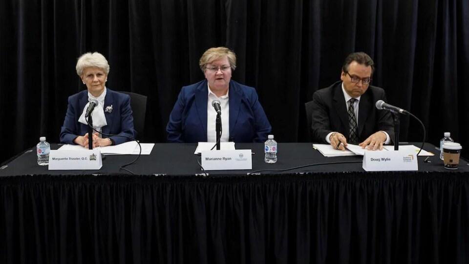 Trois personnes sont assises à une table noire. Chacun a un micro en face de lui. Un rideau noir sert de toile de fond.