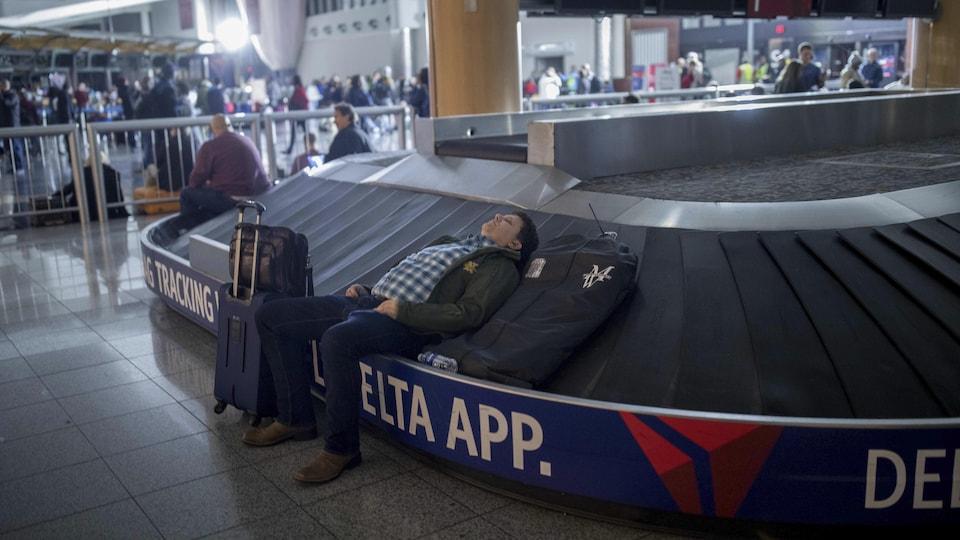 Un voyageur dort sur un carrousel à bagages à l'aéroport international Hartfield-Jackson d'Atlanta.