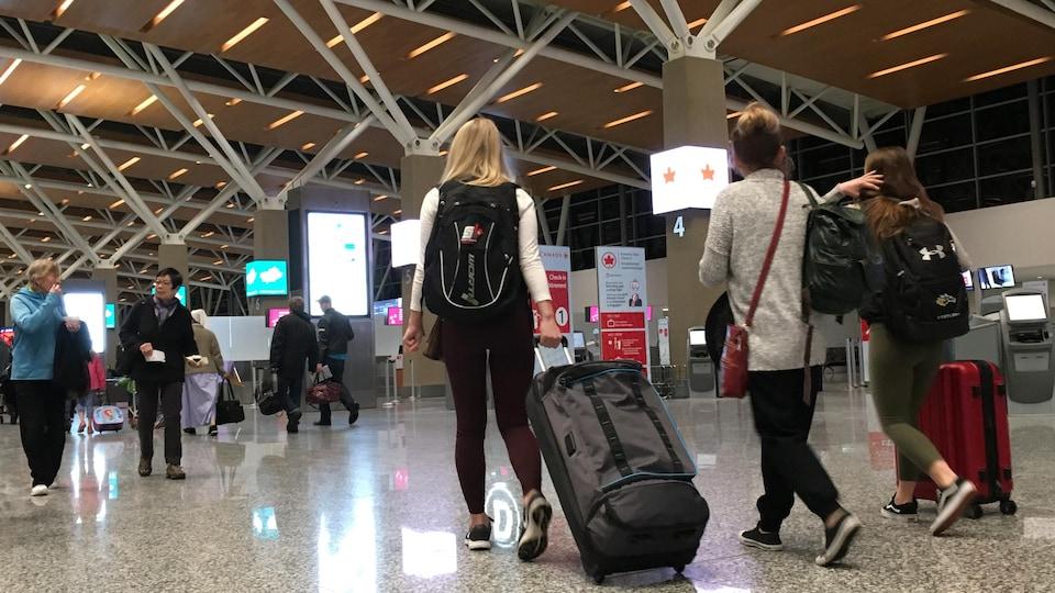 Des voyageurs, valises à la main, dans le terminal international de l'aéroport de Calgary.